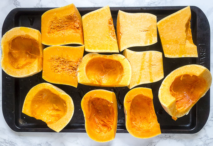 raw cut butternut squash on a baking sheet