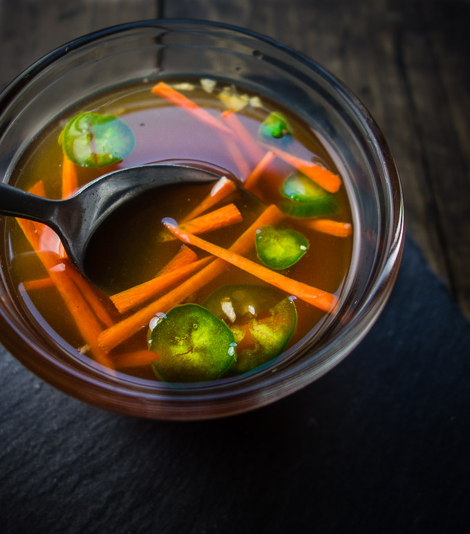 bowl of liquid with carrots and jalapenos
