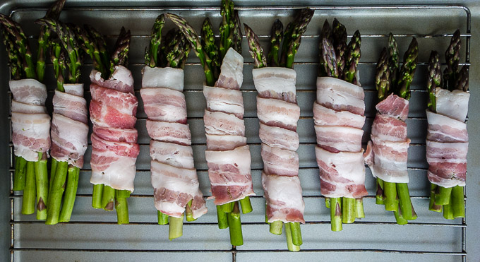 bacon wrapped around asparagus spears on a baking sheet