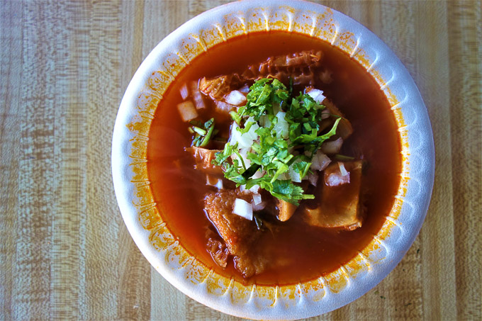 bowl of menudo with onions and cilantro