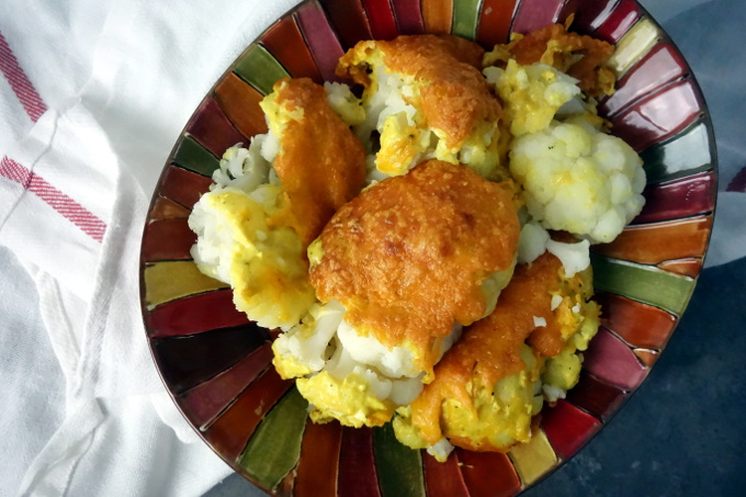 cauliflower in a colorful bowl with cheese and sauce