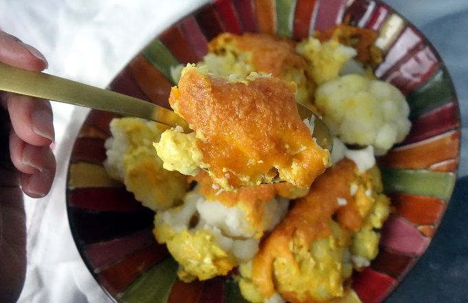 a dish of roasted cauliflower with cheese and sauce