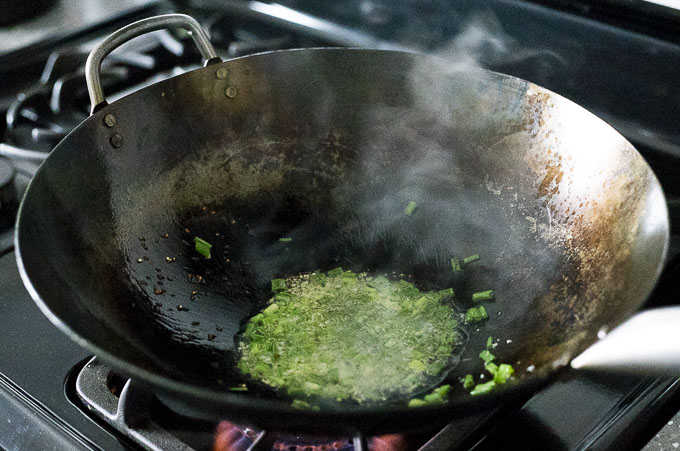 green onions and garlic in a wok