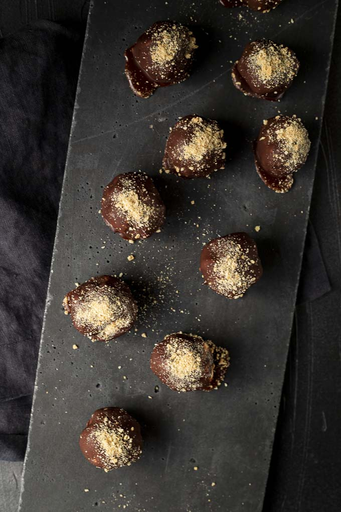 chocolate covered cheesecake bites on a platter dusted with crushed graham crackers