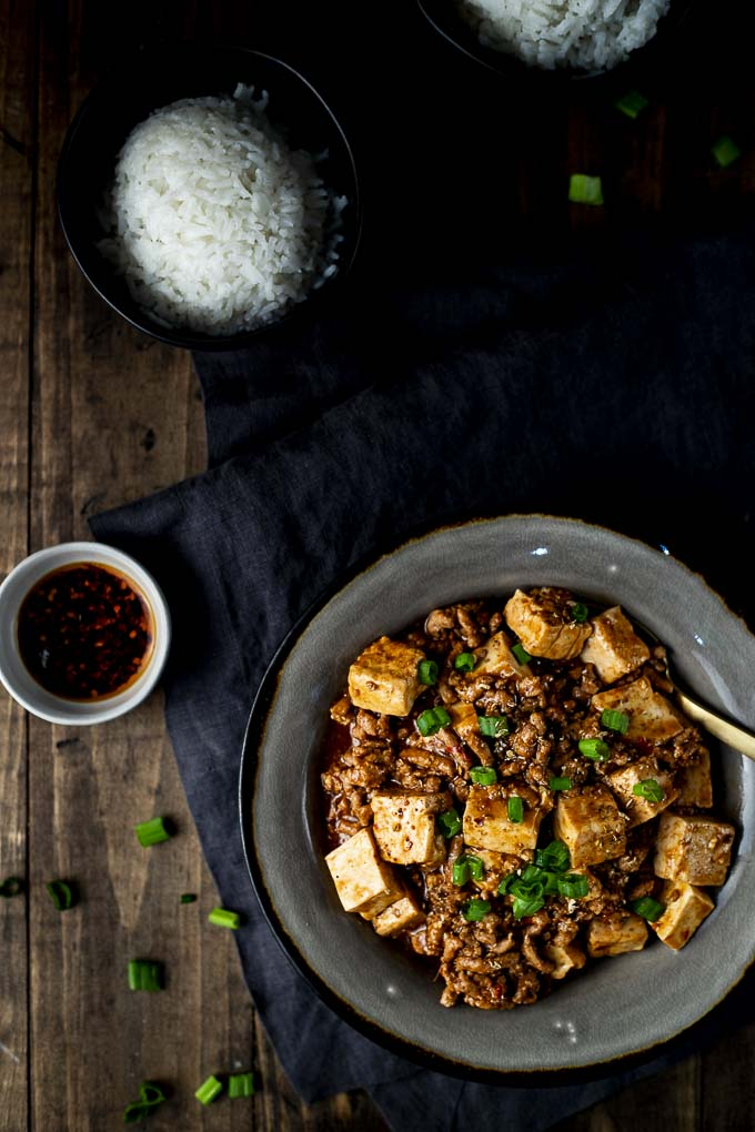 mapo tofu (ground pork and tofu) in a bowl with 2 bowls of rice and chili oil on the side