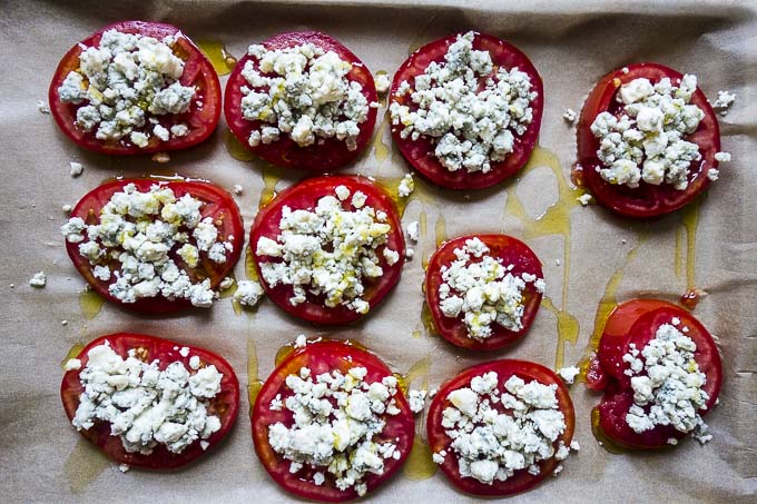 tomatoes with crumbled blue cheese on baking sheet