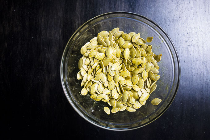 pumpkin seeds in a bowl with seasoning
