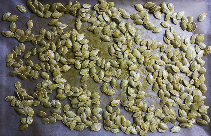 raw pumpkin seeds with seasoning on a baking sheet
