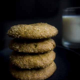 side view of gingerbread molasses cookies with glass of milk