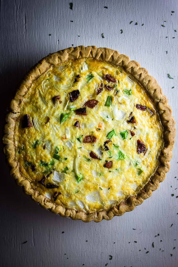 cajun shrimp and sausage quiche, egg casserole in a pie plate with peppers and sausage