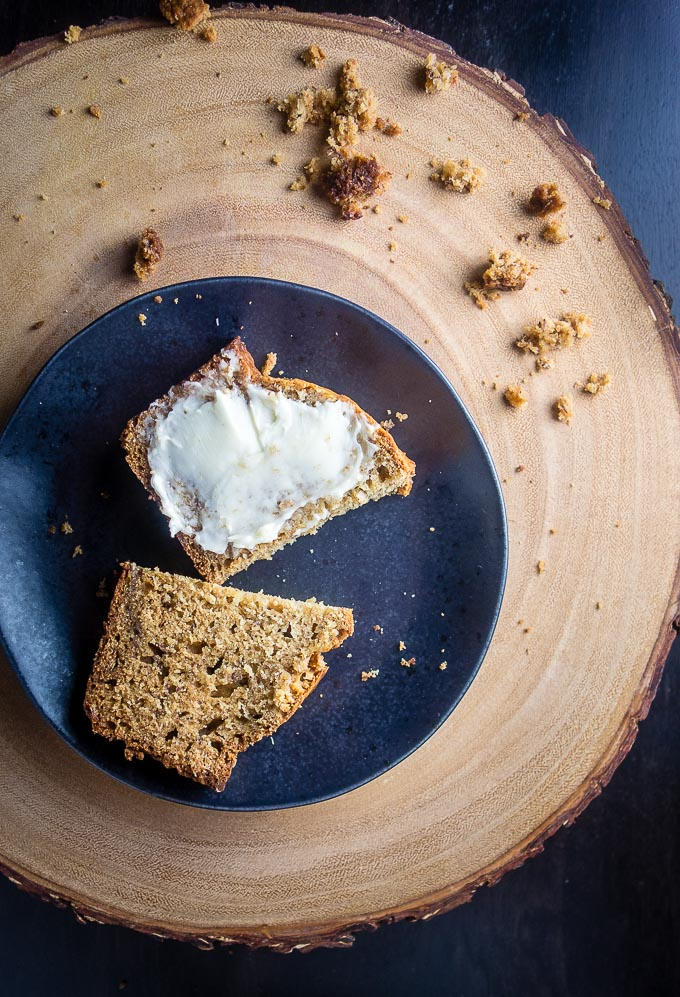 easy caramelized banana bread on a plate sliced and spread with butter