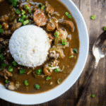 louisiana seafood gumbo with okra, seafood and sausage in roux in a bowl with rice
