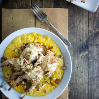 roast quail with andouille sausage cream sauce on top of grits in a bowl