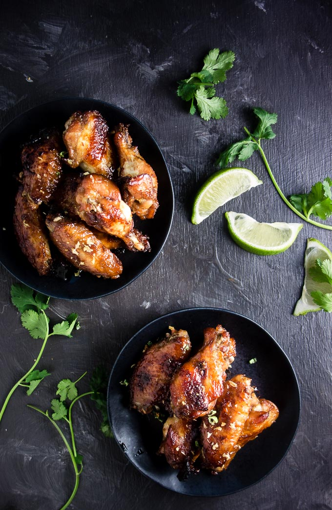 2 plates of baked vietnamese chicken wings with limes and cilantrol