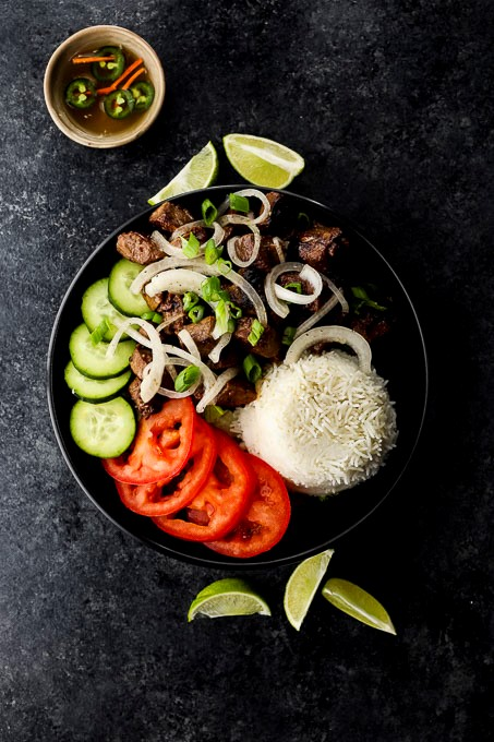 meat, vegetables and rice in a bowl covered in onions