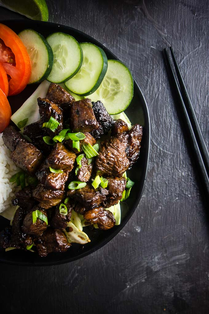 pieces of beef with cucumber, tomato, rice and green onions, chopsticks on side
