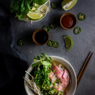 bowl of vietnamese pho with accompaniments