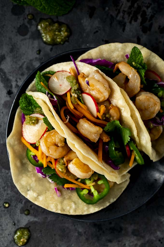 3 shrimp tacos on a plate with vegetables and salsa
