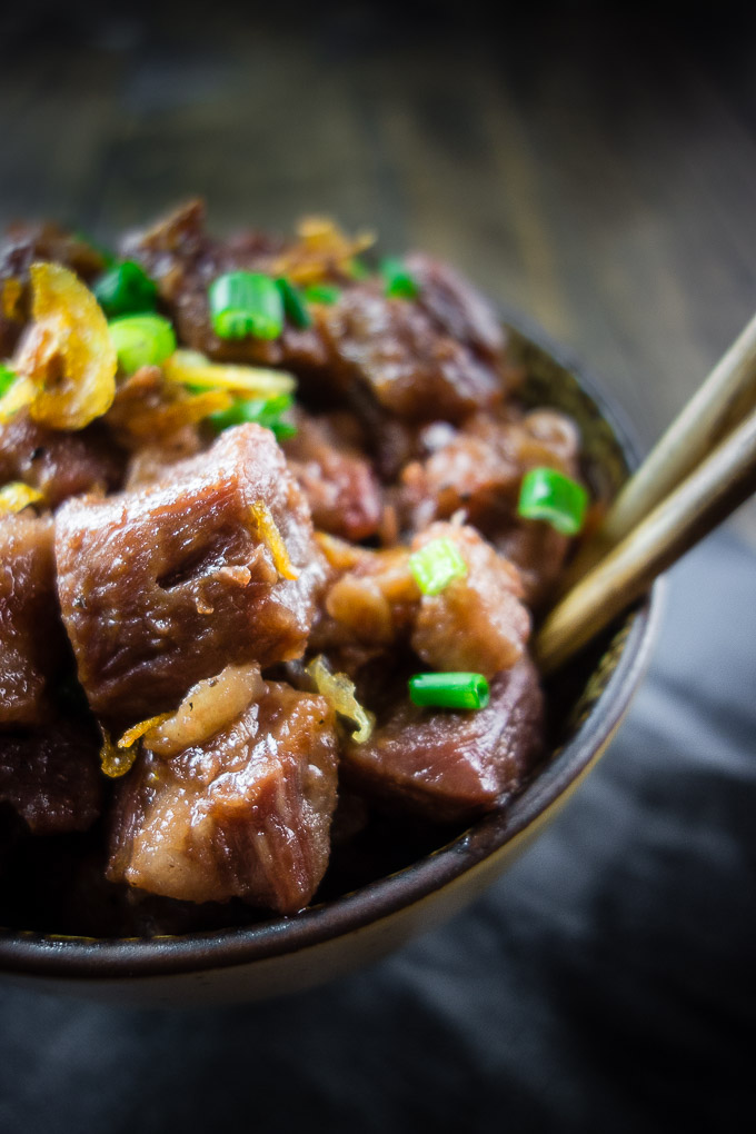 bowl of fish sauce caramelized pork pieces with green onions and chopsticks