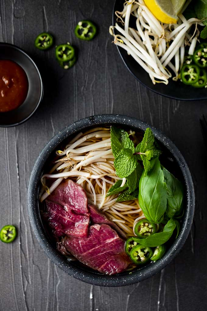 bowl of noodles soup with rare beef and herbs