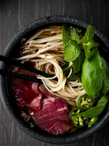 bowl of soup with beef and herbs with chopsticks