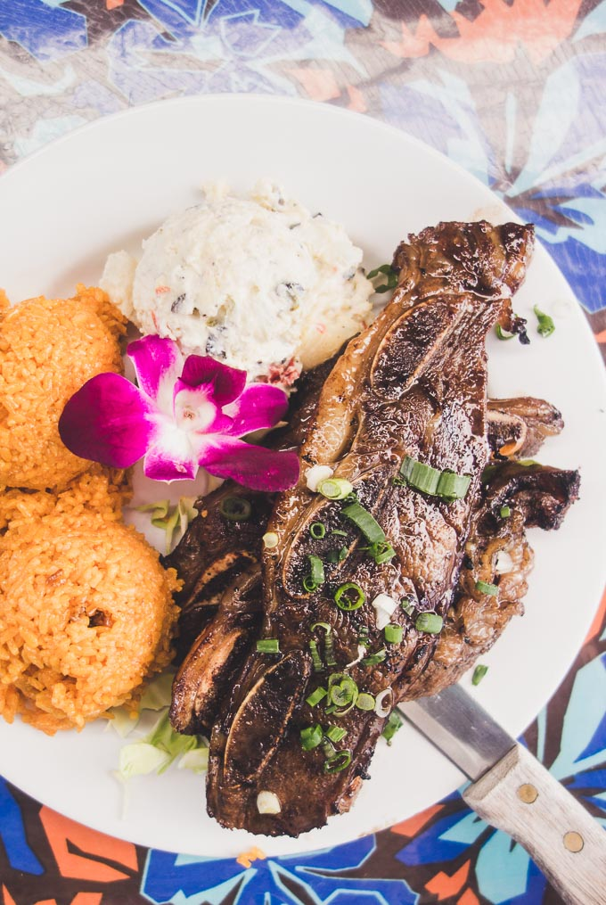 marinated kalbi ribs on a plate with red rice, potato salad and flower at matua's sushi bar and islander grill