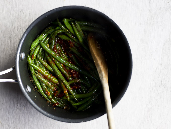 green beans, spices and chilies in a saucepan