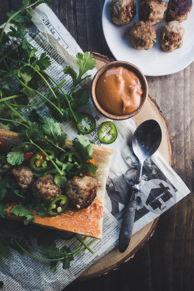 spicy meatball banh mi, meatballs on bread with cilantro and jalapenos served with sauce on the side on top of newspaper
