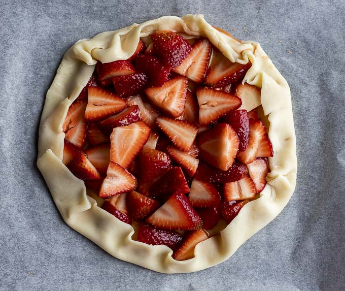 sliced strawberries folded up in a pie crust