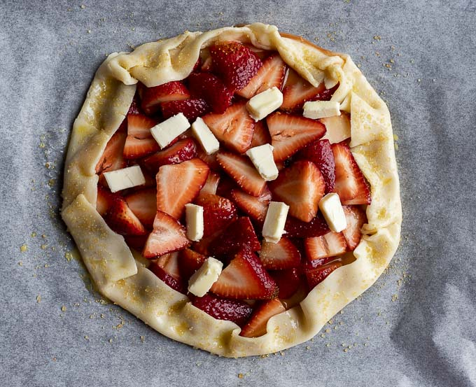sliced strawberries in pie crust with dots of butter on top