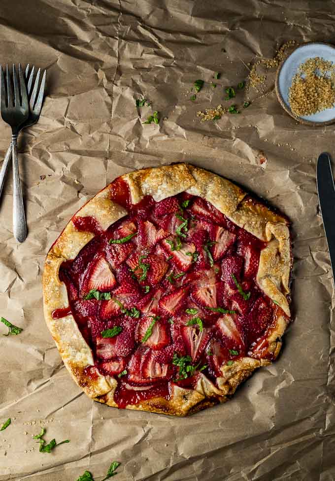 a whole galette with strawberries on parchment paper with 2 forks and a knife