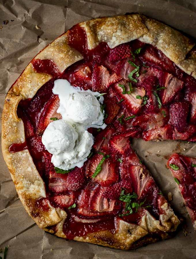 sliced strawberry galette topped with vanilla ice cream