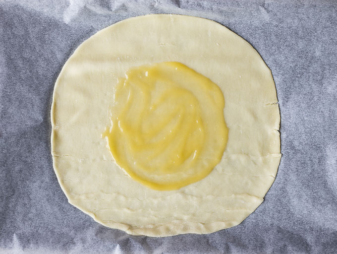 lemon curd spread on a rolled out pie crust