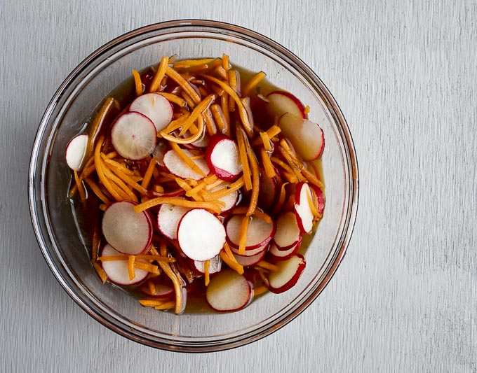 carrot and radishes in a bowl with liquid