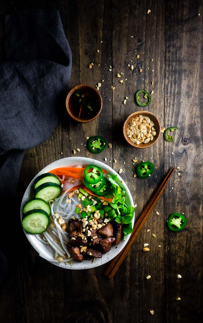 vietnamese pork noodle bowl with fresh veggies, jalapenos and herbs and peanuts and dipping sauce on the side
