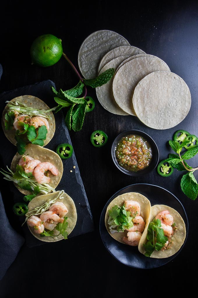 vietnamese shrimp street tacos with salsa and fresh herbs on a table