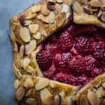 close up of raspberries in crust with almonds
