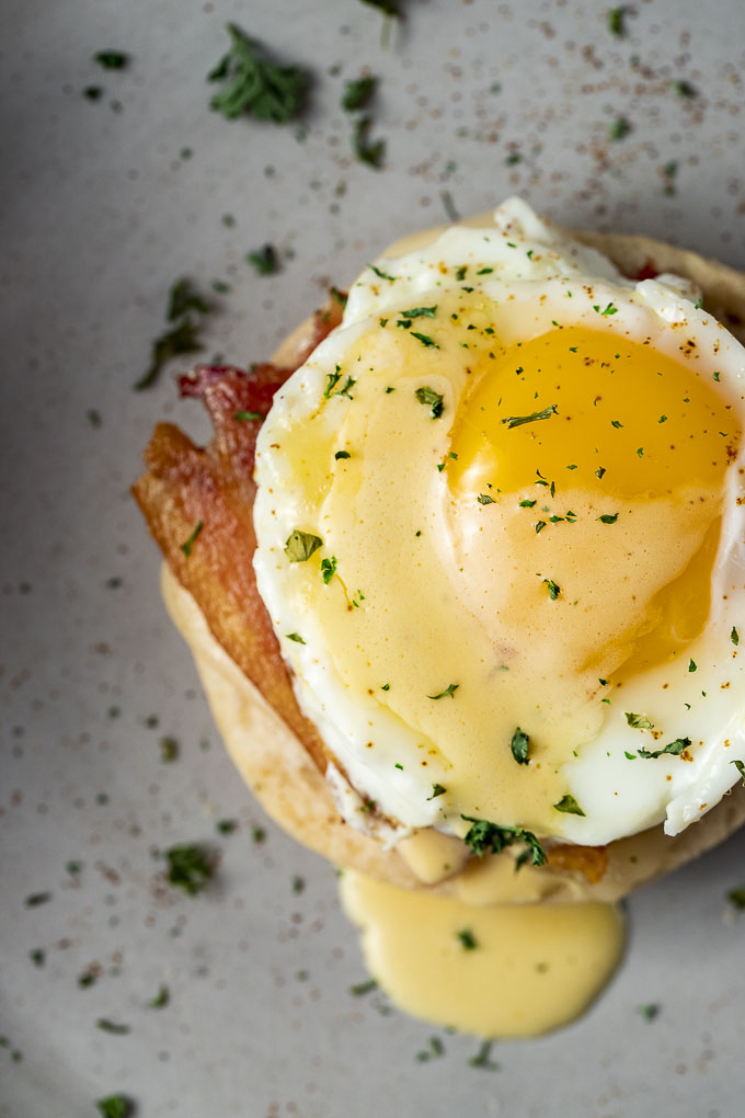 egg on top of a biscuit with hollandaise sauce on top