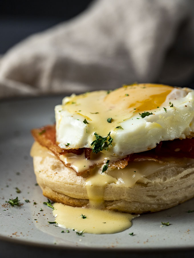 biscuit with bacon and egg on top drizzled in yellow sauce