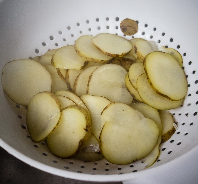 sliced potatoes in a strainer