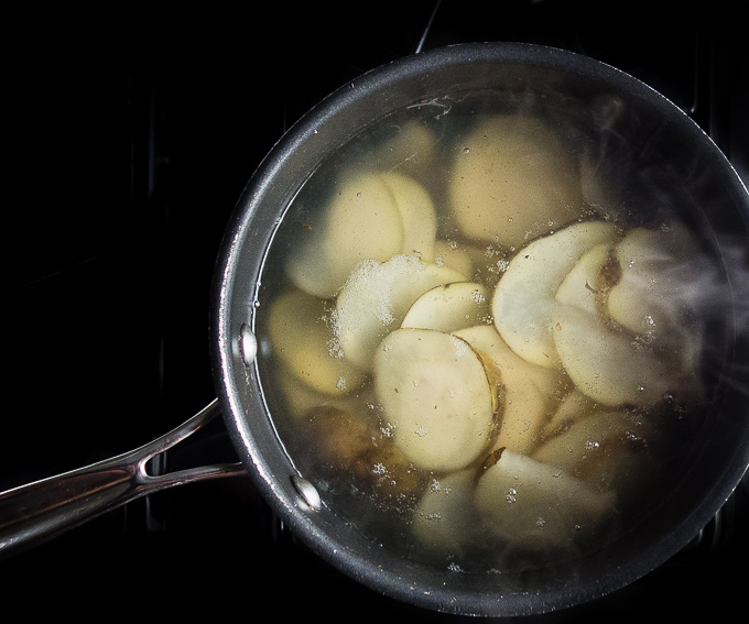 sliced potatoes in a saucepan with water
