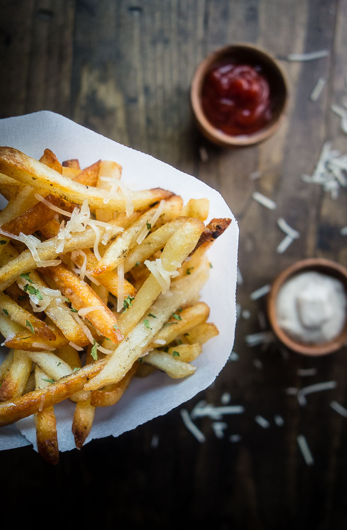 parmesan truffle fries wrapped in paper in a cup with ketchup and mayonnaise on the side
