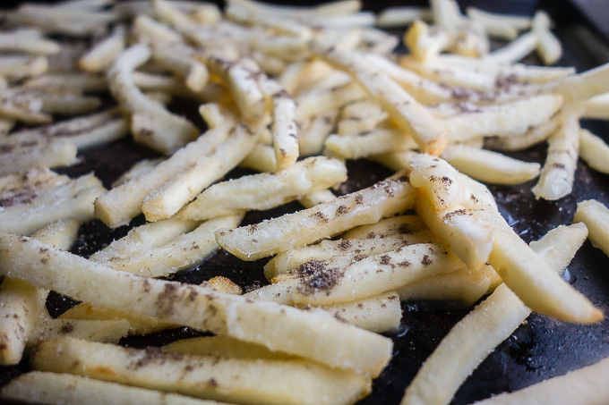 uncooked french fries on a baking sheet