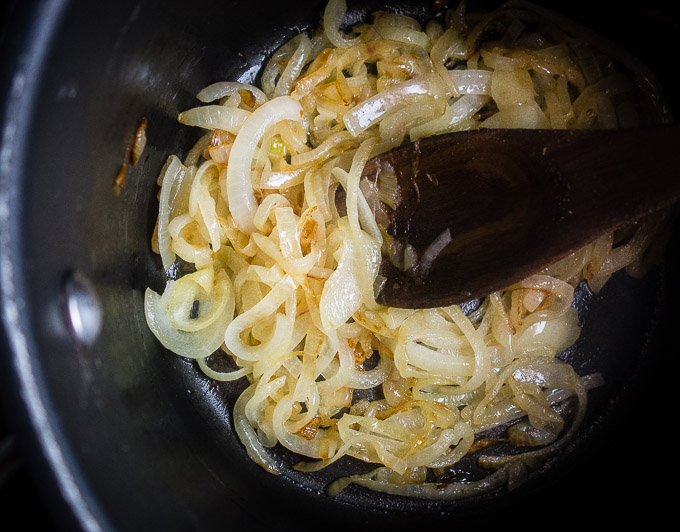 caramelized onions in a sauce pan with a wooden spoon