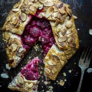 raspberries in a pie crust covered in almond - once slice taken out