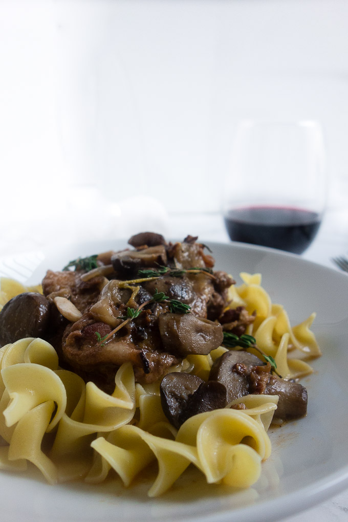 mushrooms in sauce with chicken over egg noodles with wine in background