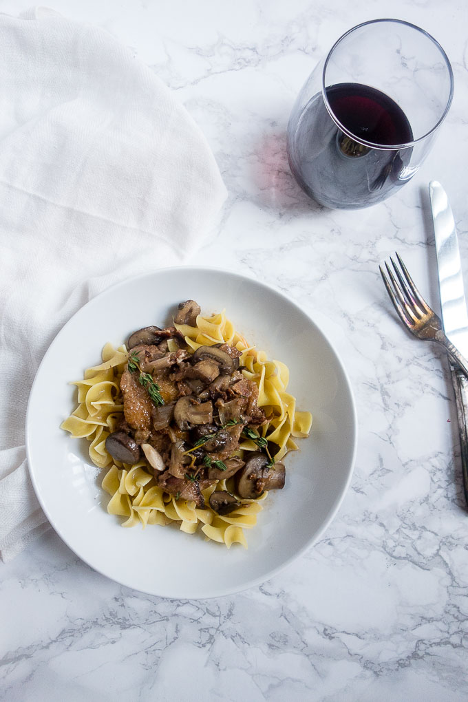 plate of noodles topped with mushrooms and chicken with glass of wine
