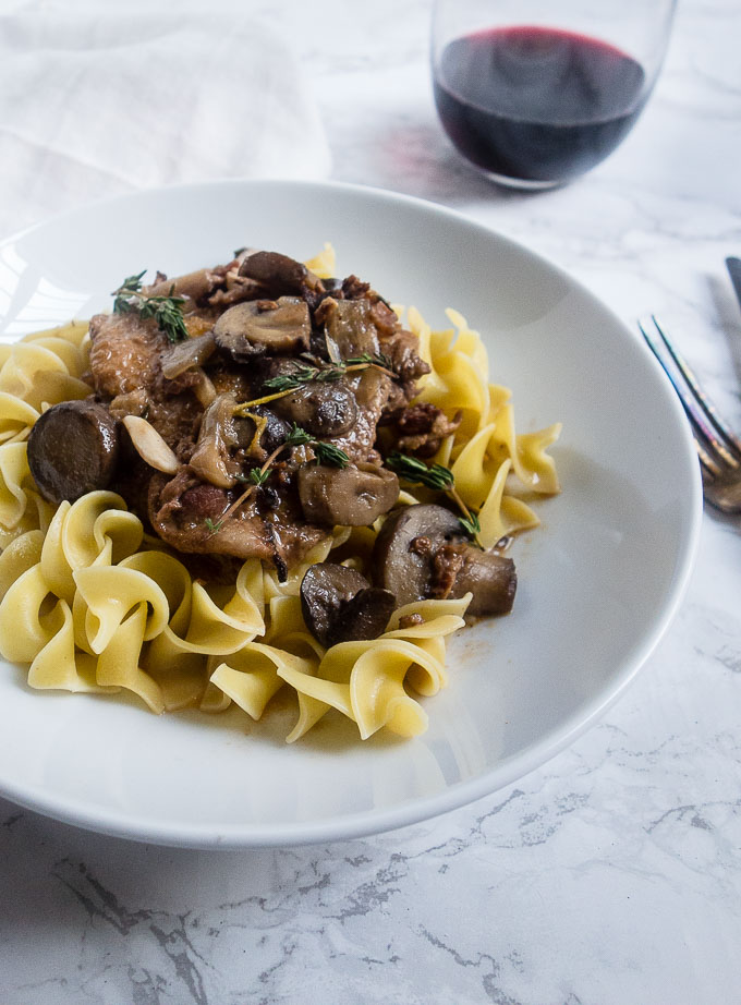 egg noodles covered with chicken and mushroom in wine sauce