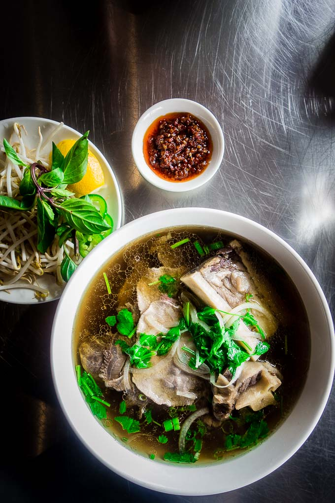 bowl of pho with meat and noodles, bean sprouts herbs and chili oil on the side