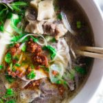 close up fo soup with meat and noodles and spicy chicli sauce